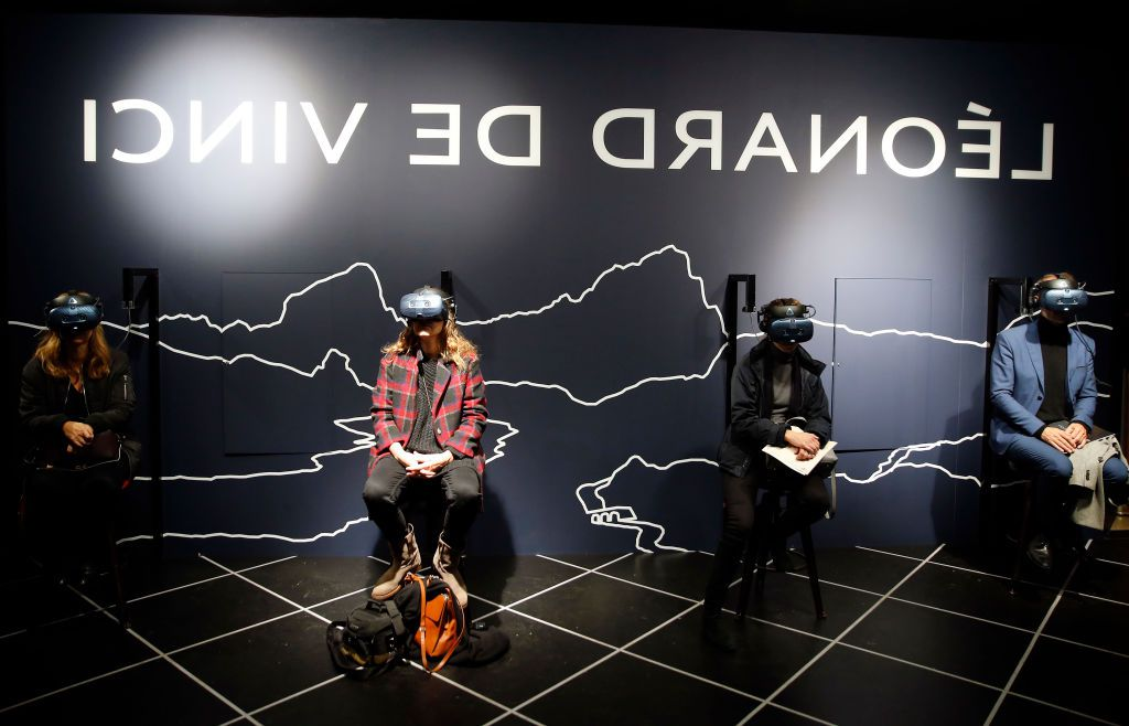 Visitors wear a virtual reality (VR) headset, while looking a virtual and interactive animations, during a press visit of the exhibition