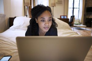 Woman Resting On Bed With Laptop