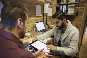Two men looking at fonts on a keyboard