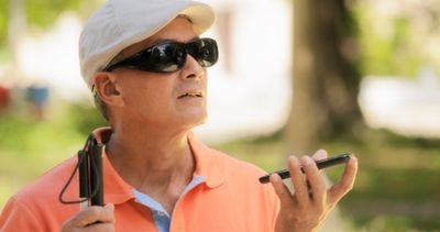 A person with vision impairment listening to a smartphone.