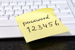 A post-it note with an an easy 123456 password written on it placed on a keyboard.