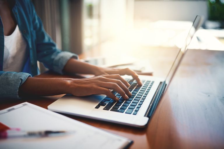 A woman typing at a laptop with a notebook by her side.