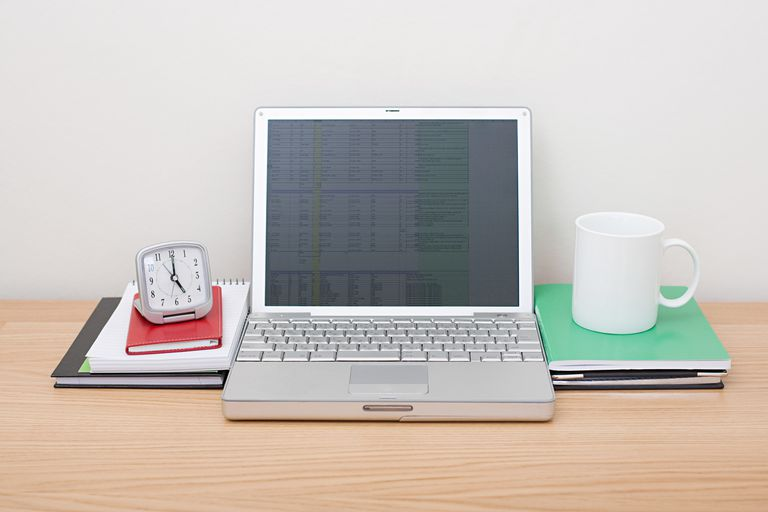 Laptop running a spreadsheet with alarm clock and mug on desk