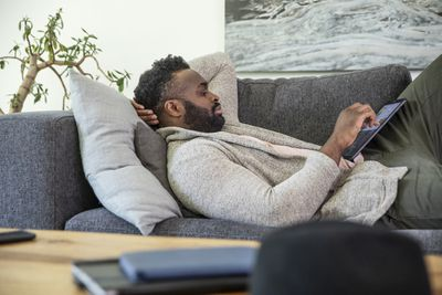Man on couch with tablet.