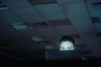 View of someone behind a laptop screen in a dark room.