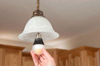 Hand installing smart light bulb into light fixture