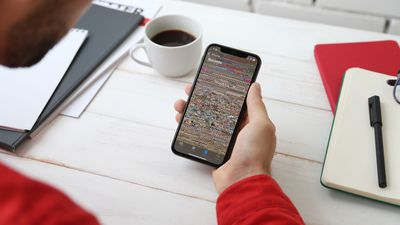 Someone holding an iPhone with hundreds of tiny photo thumbnails on the screen.