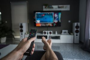 A person browsing through television channels with a remote control.