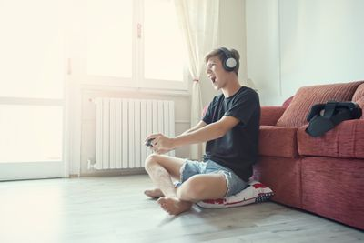 A teenage boy sitting on the floor with a games controller in his hand and headphones on his head