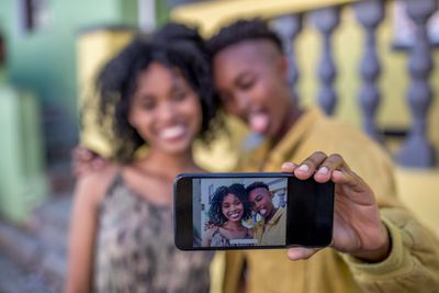 Two women taking a selfie together with the focus on the phone screen and their faces blurred