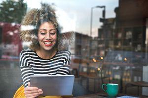 Young woman using iPad in coffee shop