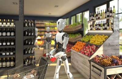 A humanoid robot with a shopping trolley is shopping at a grocery store