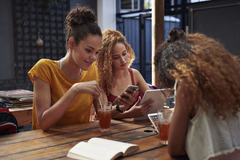 Teens use various devices at a restaurant table.