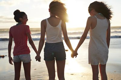 Three BFFs - Best Friends Forever - holding hands and hanging out on the beach.