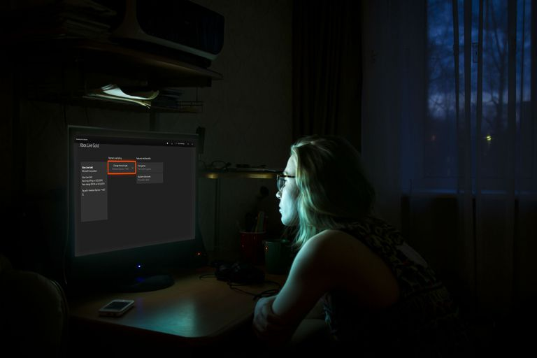 A woman in a darkened room looking at a screen showing Xbox One preferences