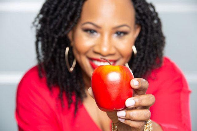 A portrait of Natalie Coleman holding an apple.