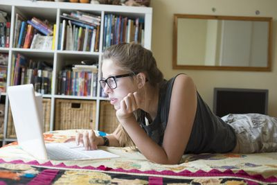 Teenage girl using laptop on bed