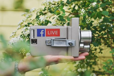 An image of a video camera with Facebook stickers on it,