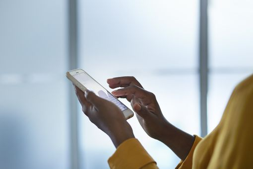 Woman in yellow shirt scrolling through white iPhone.