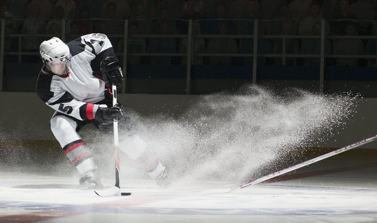Hockey player taking a shot on the ice.
