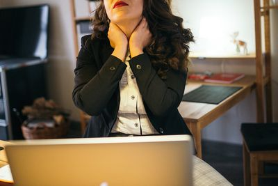Someone sitting at a laptop in a home office, rubbing their neck as if fatigued.