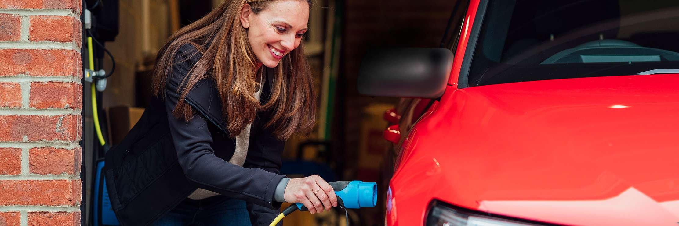 Woman charging a red EV at home in her garage.