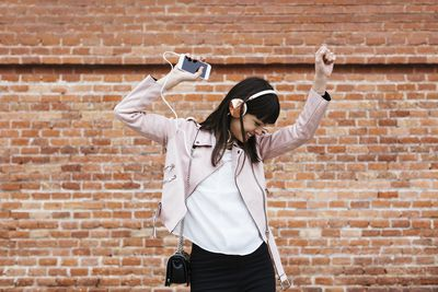 A stock photo of a woman dancing in front of a brick wall while listening to music on her smartphone using headphones.
