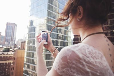 Person using smartphone to photograph Manhattan