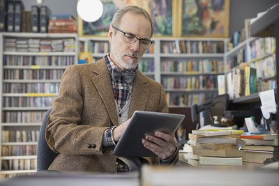 Person in office surrounded by books using iPad