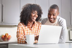 A man and woman sitting at a kitchen table smiling at a laptop screen