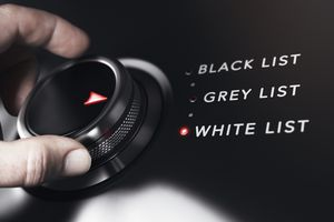 Hand turning a button with the words white, grey and black list. Anti-spam filtering concept