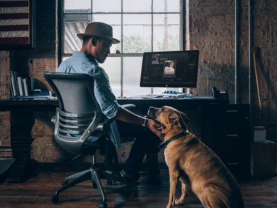 Someone at a desk in a home office, petting a dog with a Spotify share code displayed on the screen.