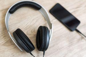 Headphones, phone on wooden table against defocused background