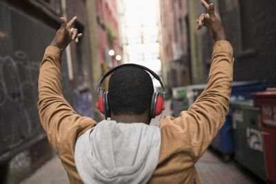 Man with headphones, listening to music, gesturing in urban alley