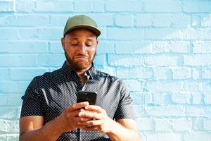 A man standing in front of a blue wall looking down at his phone and smiling