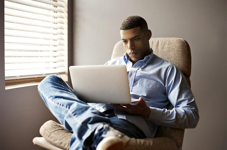 Young Man Sitting In Chair With Laptop