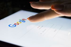 An image of a woman tapping the Google search engine on her mobile device.