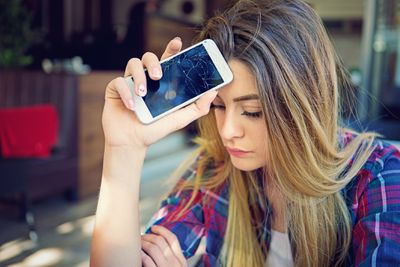 Woman holding a broken iPhone against her forehead with a disappointed look on her face.