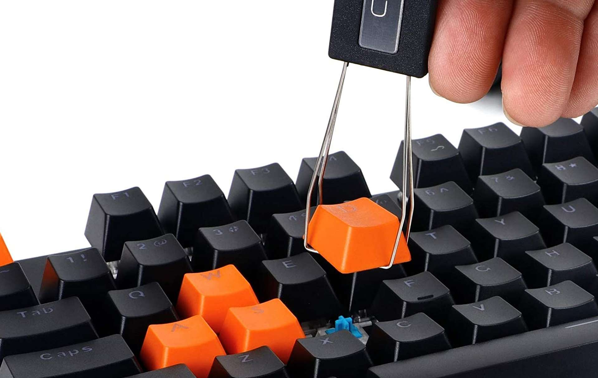 Keyboard keys being removed by a keycap puller tool.