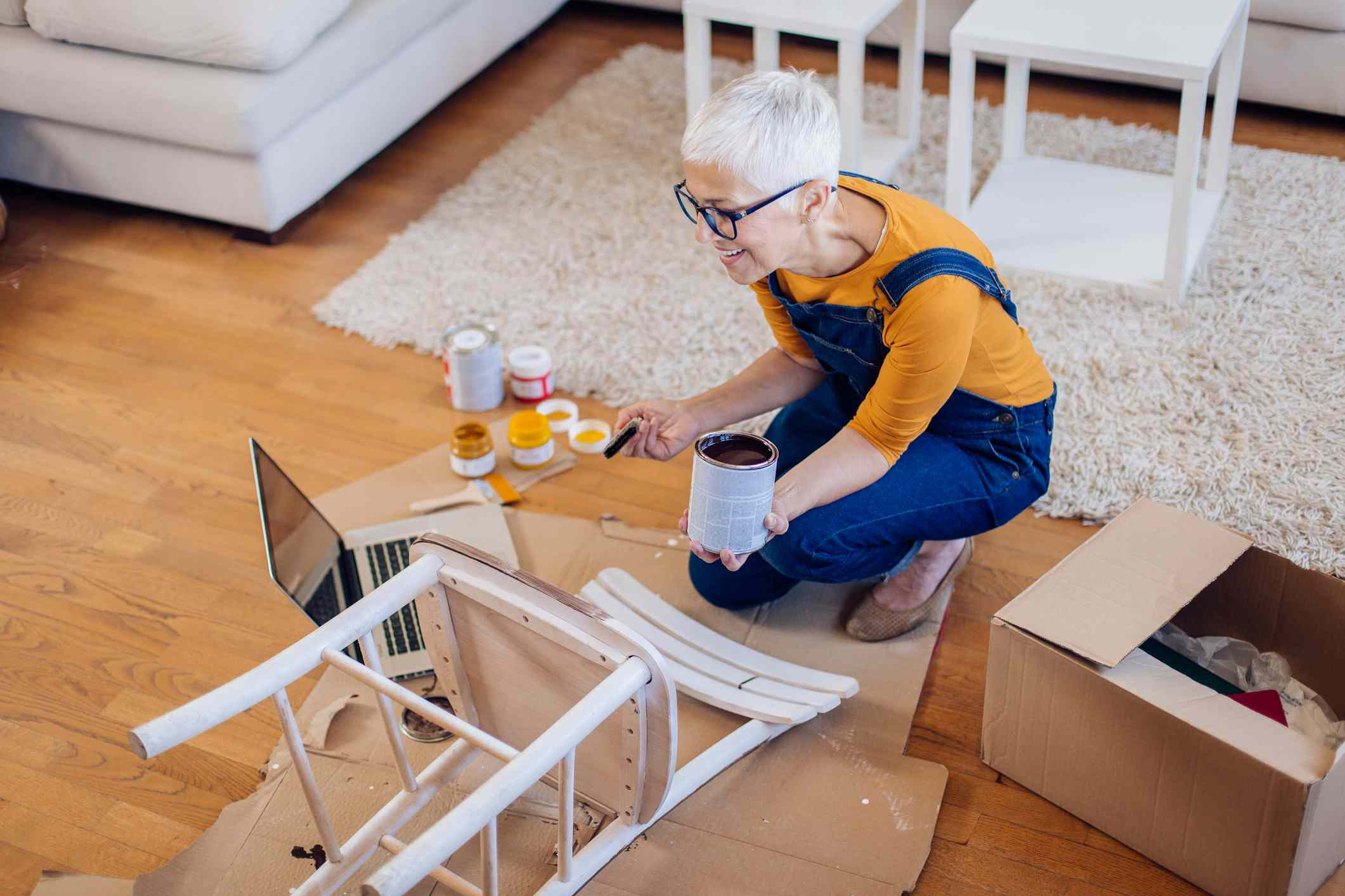 Woman watching DIY tutorials and painting a chair