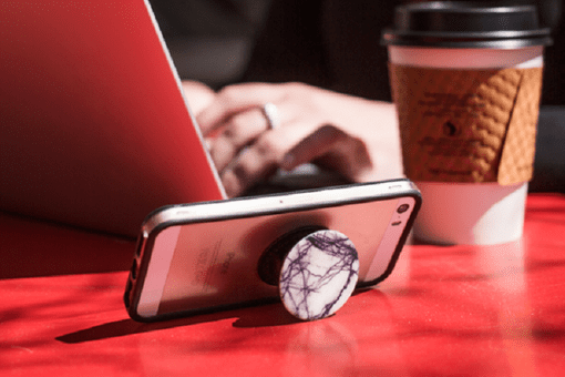 White and purple marble style PopSocket propping up iPhone on a red table.