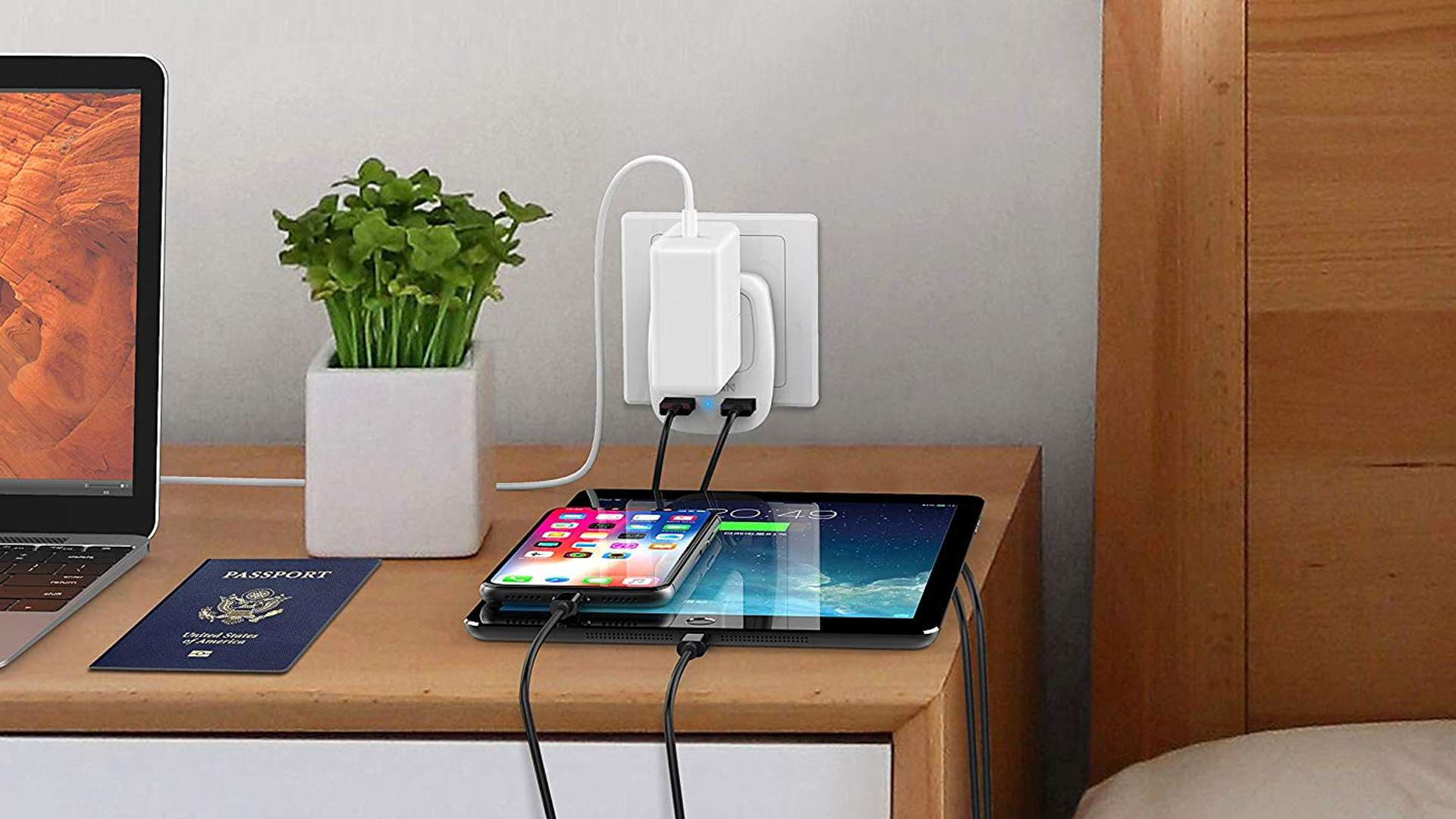 TESSAN Eurpoean and Hong Kong power adapter with USB and traditional outlet sockets charging a laptop, iPhone, and iPad..