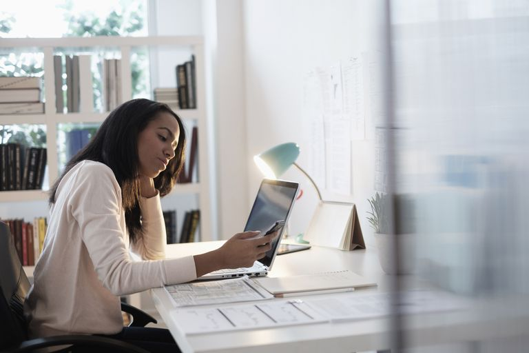 Businesswoman using cell phone at laptop in brightly lit office