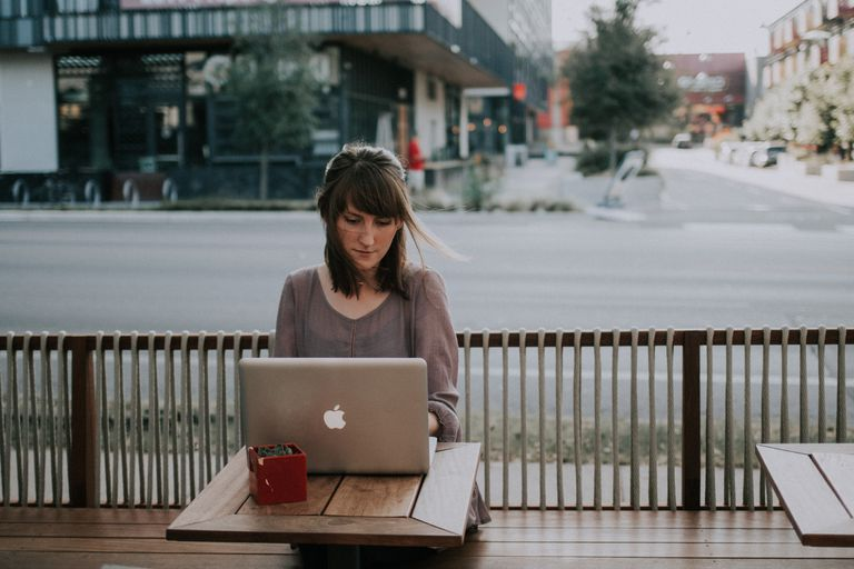 A woman using a laptop at an outside table.