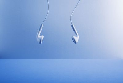 A pair of earbuds hanging from outside the frame of the image.