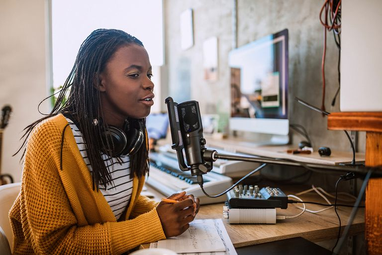 Cheerful African woman working on radio station, talking on microphone in talk show