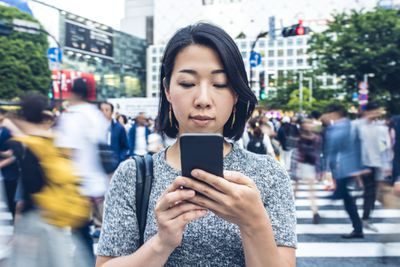 Person checking iphone on busy street