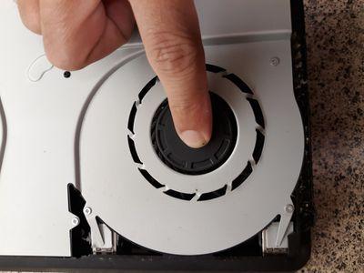 A finger holds down the fan inside a PS4 Slim model.