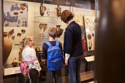 Teacher and two students looking at a museum display