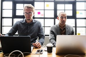 Two men working on laptops